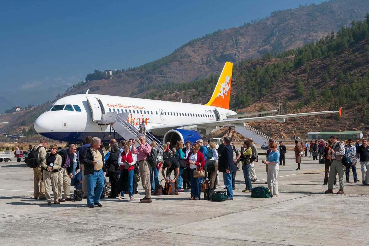 Tourists standing on the tarmac at Paro airport amazed by the scenery.